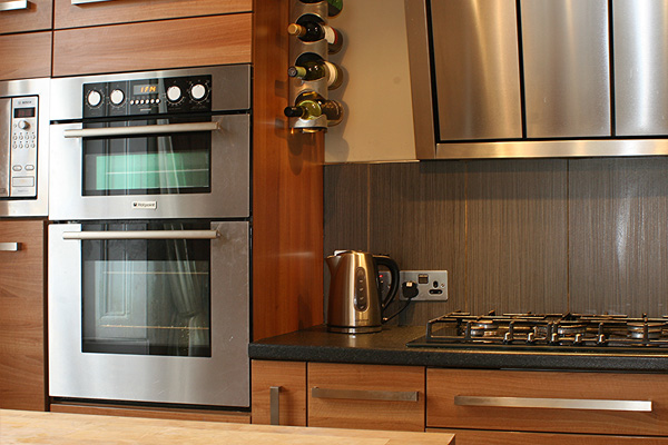 fully fitted kitchen with double electric oven, gas hob, microwave, dishwasher, coffee machine and large fridge